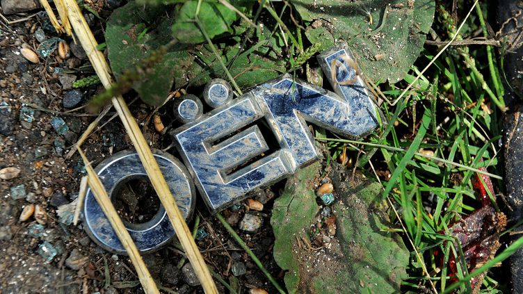 Le débris du sigle Citroën de la fourgonnette dans laquelle quatre adolescents ont été tués à Rohan, dans le Morbihan, lors de la nuit du 1er au 2 août 2015. (FRED TANNEAU / AFP)