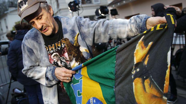 José, un fan de Johnny Hallyday venu du Brésil, déploie un drapeau acheté durant un concert, devant la maison de la star à Marnes-la-Coquette (Hauts-de-Seine), le 6 décembre 2017. (CHRISTOPHE ENA /AP / SIPA)