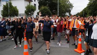 Des étudiants réalisent un haka, une danse chantée traditionnelle des îles Pacifique sud, devant la mosquée Al-Noor, en hommage aux victimes de l'attentat contre deux mosquées à Christchurch (Nouvelle-Zélande),le 18 mars 2019. (JORGE SILVA / REUTERS)