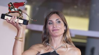 """La réalisatrice Audrey Diwan en recevant le Lion d'Or pour """"L'Evènement"""", samedi 11 septembre 2021 à Venise. (PRIMO BAROL / ANADOLU AGENCY / AFP)"""
