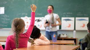 Une enfant lève la main dans une classe de Vannes (Morbihan), le 12 mai 2021. (GWENVAEL ENGEL / HANS LUCAS / AFP)