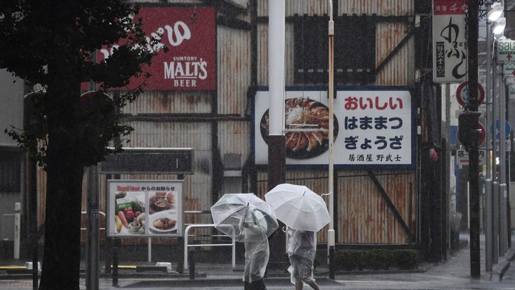 Des Japonais s'abritent du typhonHagibis, àHamamatsu le 12 octobre 2019. (ANNE-CHRISTINE POUJOULAT / AFP)