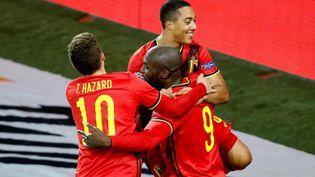 Les joueurs belgesThorgan Hazard et Youri Tielemans entourent leur coéquipier Romelu Lukaku, auteur d'un doublé contre le Danemark, le 18 novembre 2020, à Louvain (Belgique). (BRUNO FAHY / BELGA MAG / AFP)
