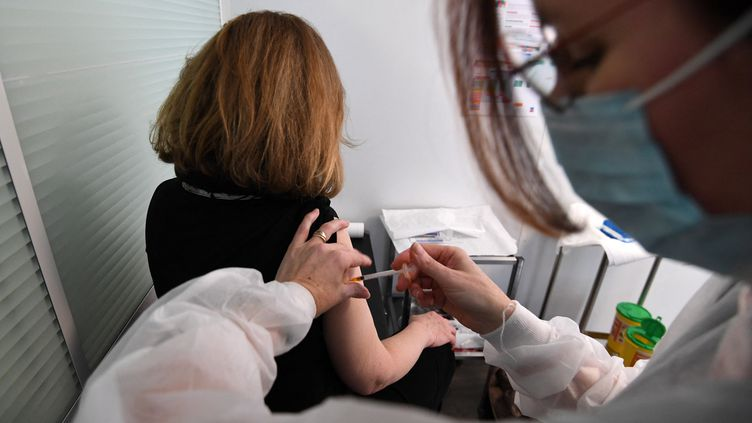 Une médecin du travail vaccine une salariée avec une dose d'AstraZeneca le 25 février 2021 à Paris. (ALAIN JOCARD / AFP)