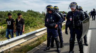 Des CRS facent à des migrants, le 5 août 2015 sur la route vers le port de Calais (Pas-de-Calais). (PHILIPPE HUGUEN / AFP)