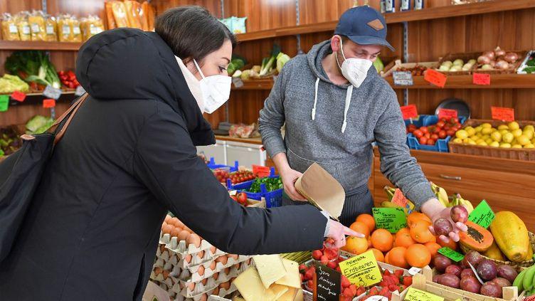 Deux personnes portent un masque FFP2 dans une épicerie de Munich (Allemagne), le 19 janvier 2021. (FRANK HOERMANN / SVEN SIMON / AFP)