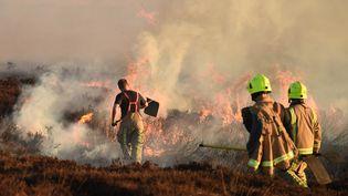 Des pompiers tentent d'éteindre un incendie dans le nord-ouest de l'Angleterre, le 27 février 2018. (OLI SCARFF / AFP)
