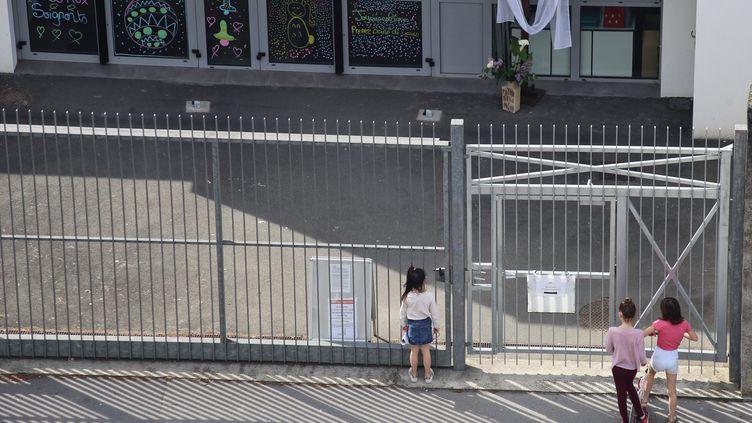 Des enfants arrêtés devant la grille de leur école, à Nantes, le 22 avril 2020. Photo d'illustration. (ROMAIN BOULANGER / MAXPPP)