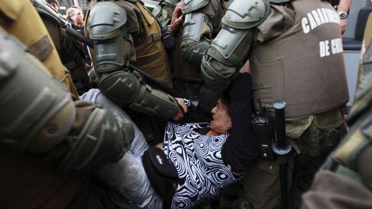 Une manifestante arrêtée lors d'une manifestation à Santiago (Chili), le 7 mars 2012, demandant des réformes contre la vie chère dans une région du sud du Chili. (VICTOR RUIZ CABALLERO / REUTERS)
