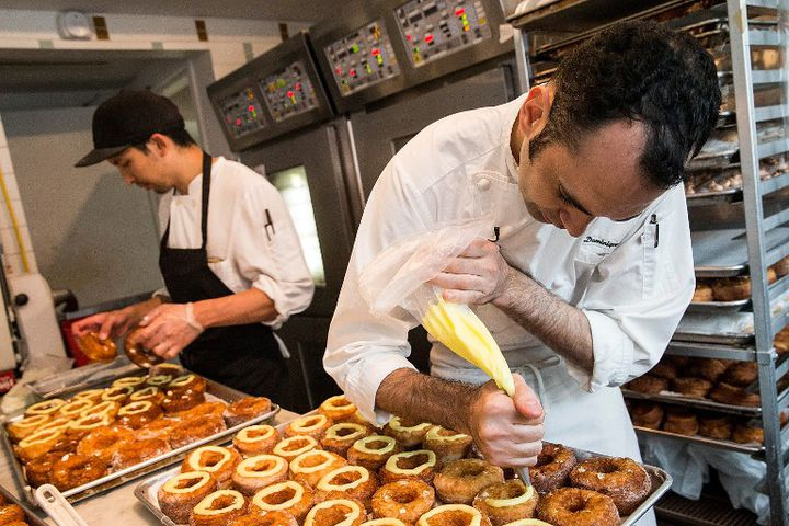 """Le chef pâtissier français Dominique Ansel prépare des """"cronuts"""" dans sa boutique new-yorkaise. (ANDREW BURTON / GETTY IMAGES NORTH AMERICA / AFP)"""