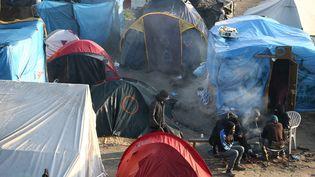 """Des migrants près de leurs tentes dans la """"jungle"""" de Calais, le 25 octobre 2016. (NEIL HALL / REUTERS)"""