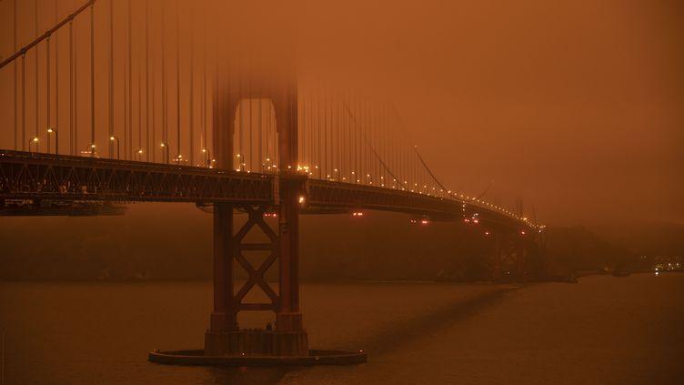 Le célèbre pont du Golden Gate, à San Francisco, enveloppée d'une fumée orange provoquée par les incendies qui ravagent la Californie, le 9 septembre 2020. (HAROLD POSTIC / AFP)