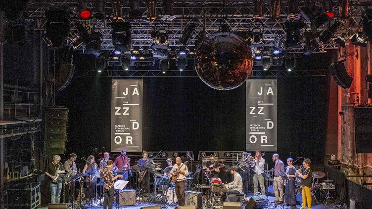 L'Orchestre national de Jazz (direction : Frédéric Maurin) le 7 juin 2019 en concert au festival Jazzdor Strasbourg-Berlin, avec entre autres Pierre Durand à la guitare, Bruno Ruder aux claviers... et en invité spécial le saxophoniste américain Tim Berne (tout à gauche en tee-shirt noir) (Patrick Lambin)