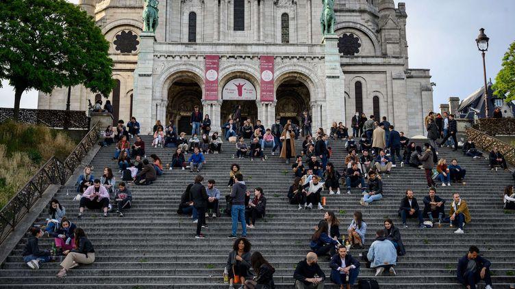 Des gens assis sur les escaliers devant la Basilique du Sacré Coeur à Paris dans le 18e arrondissement, le 12 mai 2020. (BERTRAND GUAY / AFP)