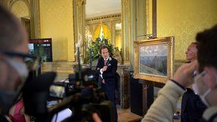 """Le commissaire priseur Aymeric Rouillac au coté de la tile de Claude Monet """"Dieppe"""" peinte en 1882, lors de sa mise en vente le 6 juin 2021 à Montbazon (Indre-et-Loire). (GUILLAUME SOUVANT / AFP)"""