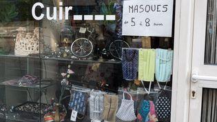 Des masques réutilisables dans la vitrine d'un magasin, à Paris, le 17 mai 2020. (RICCARDO MILANI / HANS LUCAS / AFP)