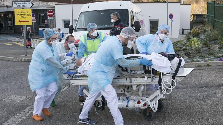 Des soignants s'affairent pour évacuer un patient de l'hôpital Emile Muller de Mulhouse, pour le transférer vers un autre établissement. (SEBASTIEN BOZON / AFP)
