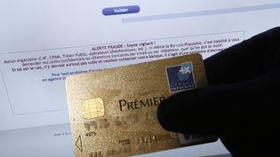 Une personne détenant une carte de crédit American Express devant un écran d'ordinateur affichant un site Internet qui porte un message d'avertissement contre la fraude. (VALERY HACHE / AFP)
