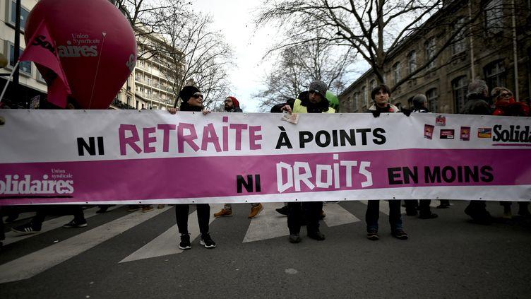 Des manifestants tiennent une banderole contre la réforme des retraites, le 11 janvier 2020 à Paris, lors d'une journée interprofessionnelle de mobilisation. (LIONEL BONAVENTURE / AFP)
