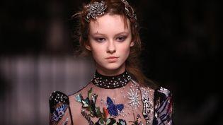 La marque phare de la mode britannique Alexander McQueen a fait son retour à Londres pour la première fois depuis 14 ans,Le défilé, organisé à Lawrence Hall, une salle d'exposition des années 1920, a offert une collection éblouissante : somptueuses robes parsemées de papillons lumineux, effets de brillance, parures étincelantes pour les cheveux, vestes spectaculaires. La marque organisait habituellement son défilé à Paris. Le fondateur de la marque, qui s'est suicidé en 2010, a été honoré en 2015 avec une rétrospective au Victoria and Albert Museum. Sarah Burton, directrice de la ligne féminine depuis 2000, est directrice de la création depuis 2010.   (JUSTIN TALLIS / AFP)