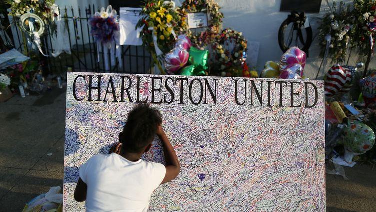 Une jeune américaine laisse un message devant l'église méthodiste de Charleston (Etats-Unis), où la tuerie s'est déroulée, le 22 juin 2015. (JOE RAEDLE / GETTY IMAGES NORTH AMERICA)