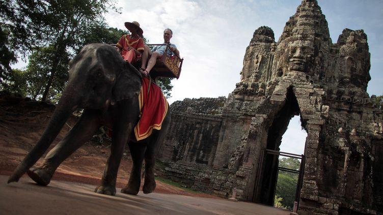 Des touristes sur le dos d'un éléphant sur le site d'Angkor, au Cambodge. (FREDRIK VON ERICHSEN / DPA)