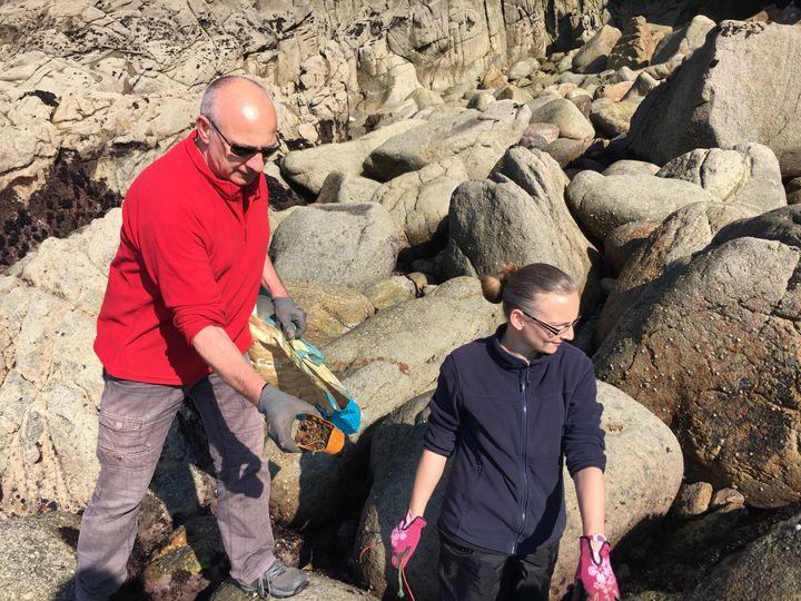 Dominique et Manon, deux bénévoles, ramassent les téléphones Garfield coincés dans les rochers, à Plouarzel (Finistère), le 22 mars 2019. (CAROLE BELINGARD / FRANCEINFO)