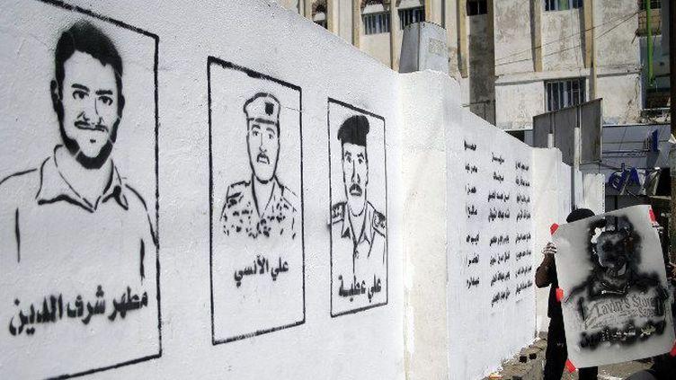 Mars 2014. Images de victimes d'un attentat revendiqué par al-Qaïda en décembre 2013 sur des murs de Sanaa en 2014. (MOHAMMED HUWAIS / AFP)