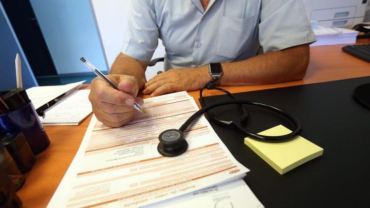 Un médecin prescrit un arrêt de travail. Photo d'illustration. (LIONEL VADAM  / MAXPPP)