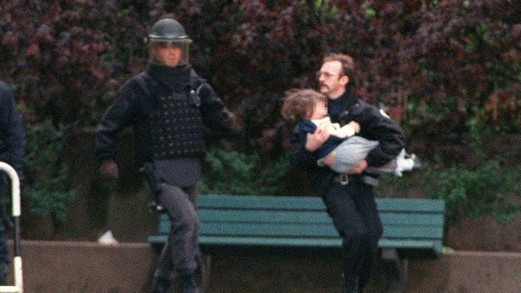 """Evacuation d'un enfant de la maternelle Charcot à Neuilly,le 15 mai 1993.Le preneur d'otages Eric Schmitt, alias """"Human Bomb"""",a été abattu de trois balles dans la tête. (PIERRE BOUSSEL / AFP)"""
