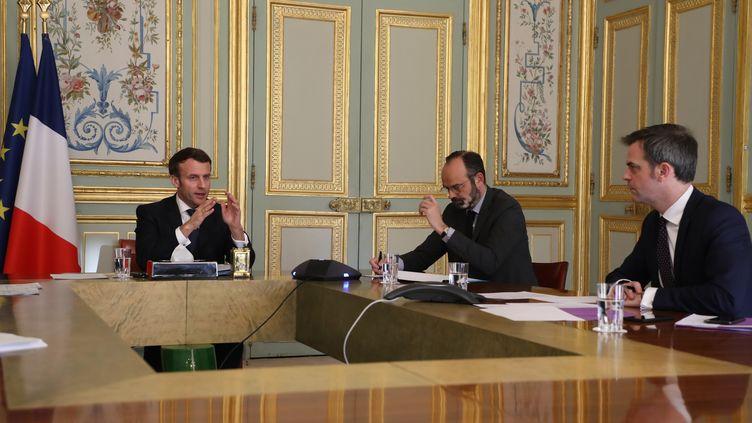 Le président de la République Emmanuel Macron, le Premier ministre Edouard Philippe et le ministre de la Santé Olivier Véran lors d'une réunion à l'Elysée en mars 2020. (LUDOVIC MARIN / AFP)
