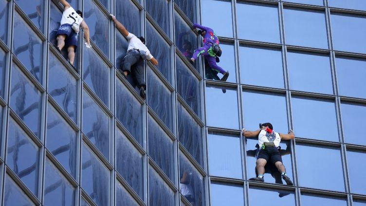 Le Français Alain Robert escalade une tour de La Défense, près de Paris, pour protester contre le pass sanitaire, le 7 septembre 2021. (THOMAS SAMSON / AFP)