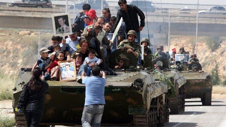 Des Syriens brandissent des portraits du président Bashar al-Assad devant un char sur la route de Deraa, le 5 mai 2011. (AFP/LOUAI BESHARA)