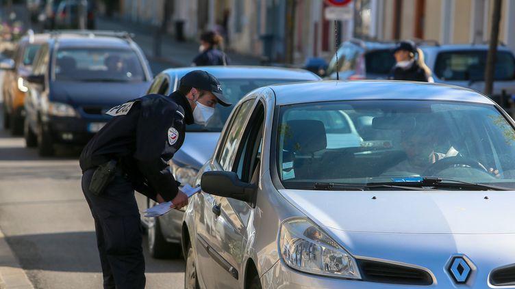 Un policier contrôle un automobiliste à Valence (Drôme), le 19 mars 2020. (NICOLAS GUYONNET / HANS LUCAS / AFP)