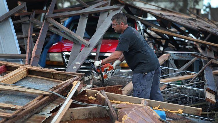 Un homme muni d'une tronçonneuse au milieu des décombres après le passage de l'ouragan Laura, à Lake Charles, en Louisiane (Etats-Unis), le 28 août 2020. (JOE RAEDLE / GETTY IMAGES NORTH AMERICA / AFP)