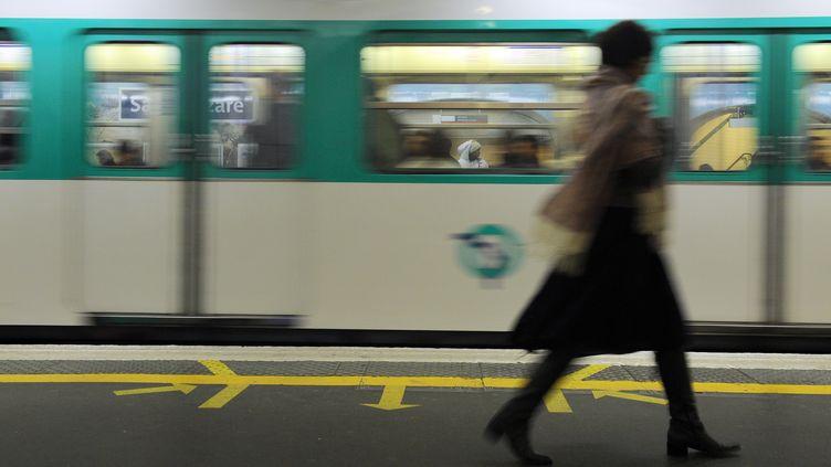Une femme passe devant une rame de métro parisien, le 28 octobre 2010. (MIGUEL MEDINA / AFP)