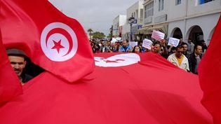 Un drapeau déployé dans une manifestation à Djerbapour la démocratie et contre le terrorisme,le 29 mars 2015, deux jours après l'attentat meurtrier du Bardo à Tunis. (ROBERT MICHAEL / AFP)