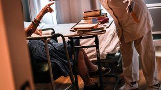 Un résident d'Ehpad en discussion avec une infirmière (illustration).   (STEPHANE DE SAKUTIN / AFP)
