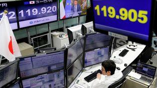 Un trader surveille les conséquences du rejet du référendum italien depuis la bourse de Tokyo (Japon), le 5 décembre 2016. (TORU HANAI / REUTERS)