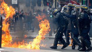Des agents des forces de l'ordre visés par des cocktails molotov, à Paris, en marge d'un défilé du 1er-Mai, le 1er mai 2017. (GONZALO FUENTES / REUTERS)