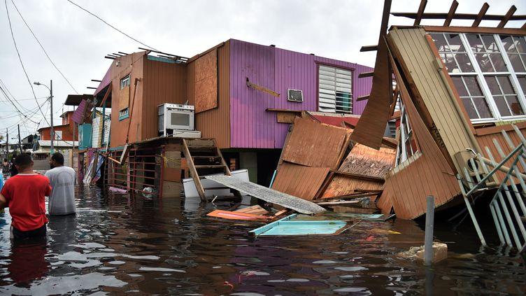 Des Portoricains marchent dans les rues inondées de Juana Matos, après le passage de l'ouragan Maria, le 21 septembre 2017. (HECTOR RETAMAL / AFP)