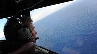 Un militaire néo-zélandais recherche le vol MH370 au large de la côte ouest de l'Australie, le 13 avril 2014. (GREG WOOD / POOL)