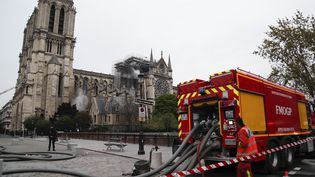 Depuis le quai Saint-Michel, les pompiers autour de Notre-Dame de Paris, au matin du 16 avril 2019. (ZAKARIA ABDELKAFI / AFP)