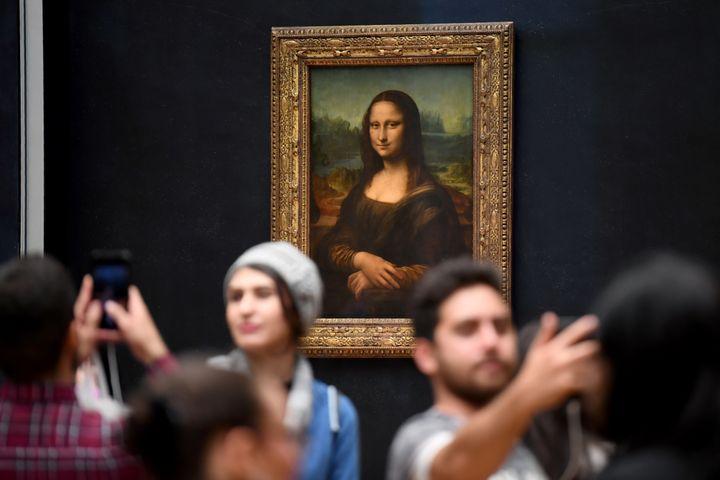 """Des visiteurs se prennent en photo devant """"La Joconde"""" au musée du Louvre (ERIC FEFERBERG / AFP)"""