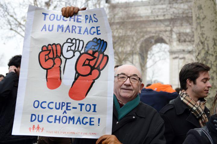 Un homme tient une pancarte anti-mariage pour tous, à Paris, le 24 mars 2013. (ERIC FEFERBERG / AFP)