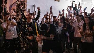 Des militants pro-démocratie célèbrent la victoire d'un candidat pro-démocratie, dans le district de Tuen Mun, à Hong Kong, le 25 novembre 2019. (PHILIP FONG / AFP)