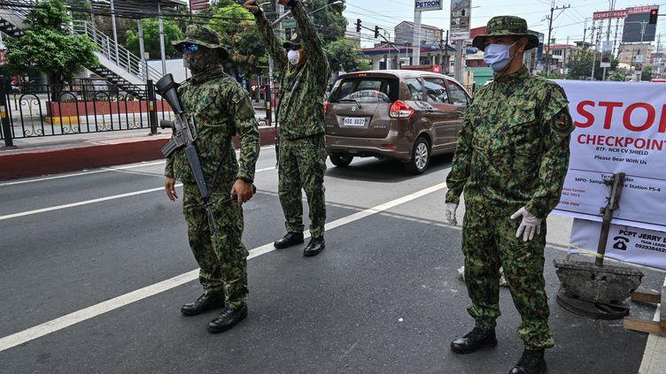Des policiers philippins surveillent un checkpoint à la frontière entre Quezon city et Manille, le 18 mars 2020. (TED ALJIBE / AFP)