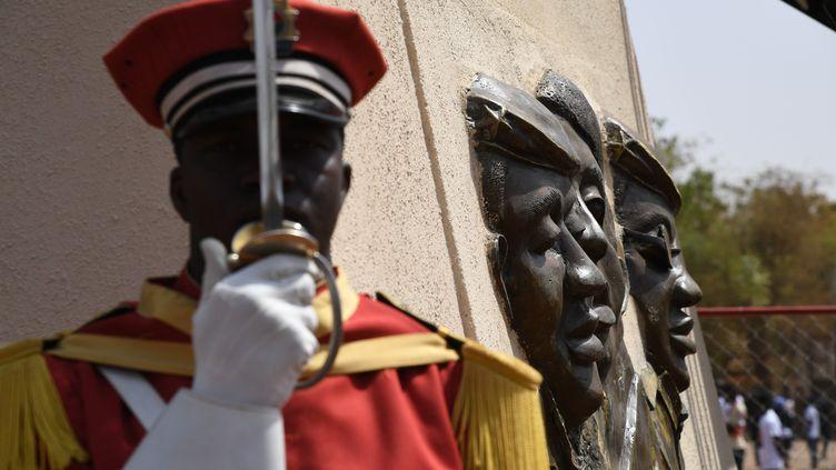 Un membre de la garde d'honneur se tient sous la statue de bronze de l'ancien président du Burkina Faso, Thomas Sankara, le jour de l'inauguration de son mémorial au Conseil de l'Entente de Ouagadougou, le 2 mars 2019. (ISSOUF SANOGO / AFP)