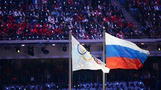Les drapeaux russe et olympique lors de la cérémonie de clôture des JO de Sotchi le 23 février 2014. (VALERIY MELNIKOV / RIA NOVOSTI / AFP)