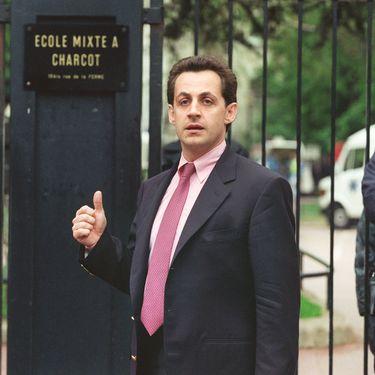 """Le maire de Neuilly-sur-Seine (Hauts-de-Seine), Nicolas Sarkozy, devant l'école Commandant Charcot où plusieurs enfants sont retenus en otages par Eric Schmitt, alias """"Human Bomb"""", le 13 mai 1993. (PASCAL PAVANI / AFP)"""